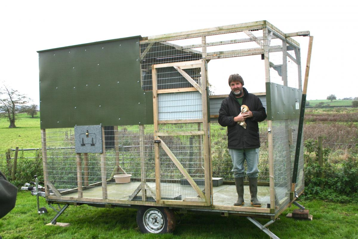 John placing a rehab barn owl in our mobile aviary ready to be returned to the wild.